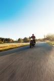 En ung man som rider en avbrytare på en väg royaltyfri bild