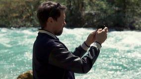 En ung man som rymmer en smartphone och fotograferar flodsängen i sommaren stock video