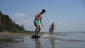 En ung man som skimboarding på den lösa stranden stock video