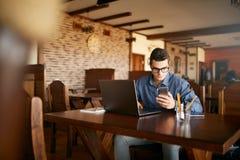 En ung man som skriver en text på den mobila moderna smartphonen Hipster som rymmer en modern telefon och skriver ett telefonmedd Fotografering för Bildbyråer