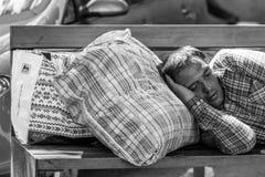 En ung man som sover på en bänk nära den Bucharest drevstationen Arkivbild