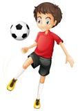 En ung man som spelar fotboll Arkivbild