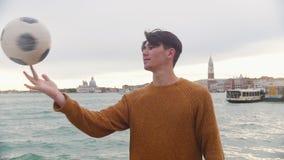 En ung man som spelar med en boll p? st?llningen p? en bakgrund av havet Rotering av bollen p? hans finger arkivfilmer