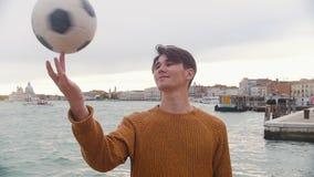 En ung man som spelar med en fotbollboll p? st?llningen p? en bakgrund av havet Rotering av bollen p? hans finger stock video