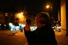 En ung man som tar för att ta foto i Edinburg på natten royaltyfria foton