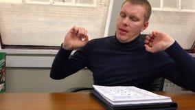 En ung man sträcker hans fåtölj och sätter hans huvud på hans händer lager videofilmer