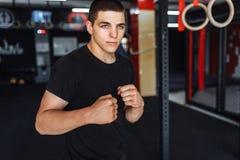 En ung man utbildar i idrottshallen, skakar på idrottshalltricepens och bicen royaltyfri foto