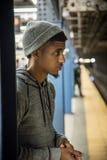 En ung man väntar på ett drev på en NYC-gångtunnelplattform Royaltyfri Foto