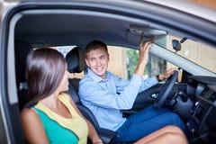 En ung man visar hans flickvän en ny bil Begreppet av att köpa en ny bil royaltyfria bilder