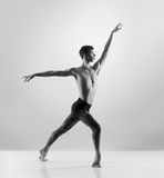 En ung manlig dansare som utför en flyttning på grå färger arkivbild