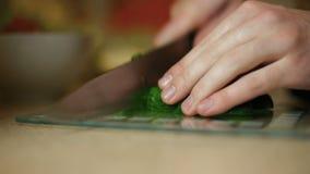 En ung manlig grabb skivar en gurka på ett glass bräde i köket lager videofilmer