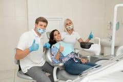 En ung manlig tandläkare, hans assistent och lyckliga kvinnliga tålmodiga tummar upp Plats för tandläkarekontorslivsstil Doktorsö royaltyfri foto