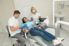 En ung manlig tandläkare och en lycklig kvinnlig patient Plats för tandläkarekontorslivsstil Doktorsövning Tålmodig hälsovård arkivfoton