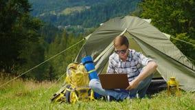 En ung manlig turist använder en bärbar dator i campa nära ett tält I ett pittoreskt ställe i bakgrunden av bergen Royaltyfri Bild