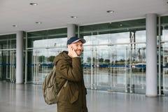 En ung manlig turist på flygplatsen eller nära en köpcentrum eller en station kallar en taxi eller talar på en mobiltelefon eller arkivfoto