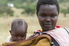 En ung Masaimoder med henne behandla som ett barn Arkivbild
