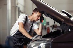 En ung mekaniker förbryllas, medan arbeta på en bilservice och underhåll arkivbilder