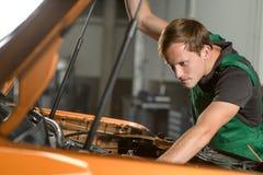 En ung mekaniker i gröna overaller reparerar en auto motor royaltyfri foto