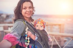 En ung moder är på stranden med henne behandla som ett barn i en rem Royaltyfri Foto