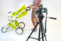 En ung moder i en rosa klänning rymmer vid handtaget av en sittvagn vid hennes händer En skärm av kameran fokuseras på arkivbilder