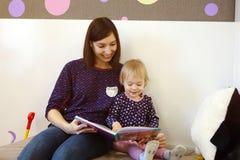 En ung moder läser en bok för barn` s för ett barn Fotografering för Bildbyråer