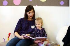 En ung moder läser en bok för barn` s för ett barn Arkivbilder