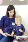 En ung moder läser en bok för barn` s för ett barn Arkivfoton