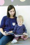 En ung moder läser en bok för barn` s för ett barn Royaltyfri Foto