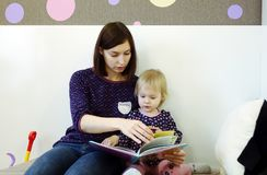 En ung moder läser en bok för barn` s för ett barn Royaltyfri Fotografi