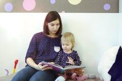 En ung moder läser en bok för barn` s för ett barn Arkivfoto