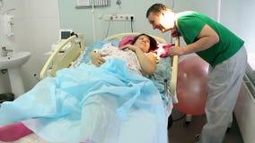 En ung moder ligger med ett nyfött i förlossningsavdelningen Koppla av efter barnsbörd Den lyckliga fadern kysser henne stock video