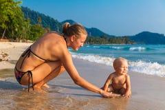 En ung moder med ett barn som har gyckel på en tropisk strand nat Royaltyfria Foton