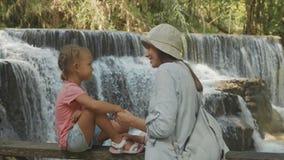 En ung moder och hennes gulliga dotter som vilar mot kaskaden av en vattenfall lager videofilmer