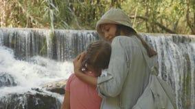 En ung moder och hennes gulliga dotter som vilar mot kaskaden av en vattenfall arkivfilmer
