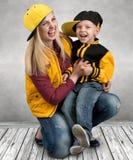 En ung moder och en liten son i stilen av höftflygtur Trendig familj Den unga rapparen kall dj royaltyfri foto