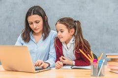 En ung moder och en skolflickablick i en grå bärbar dator p? en gr? f?rgbakgrund Frun skriver ord på bärbara datorn arkivbilder