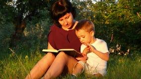 En ung moder och son sitter under ett träd i parkera i solen och läsningen en bok Förhållandet between lager videofilmer