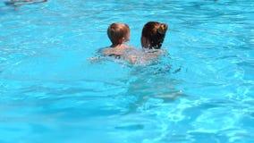 En ung moder undervisar hennes lilla son att simma i pölen i sommaren stock video