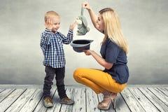En ung moder visar hennes unga son trickkaninen i hatten Familjunderhållning royaltyfri foto