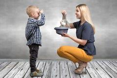 En ung moder visar hennes unga son trickkaninen i hatten Familjvänskapsmatch, underhållning royaltyfria foton
