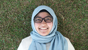 En ung moslemflicka som lägger på grönt gräs royaltyfria foton