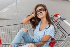 En ung nätt mörker-haired flicka med exponeringsglas, bärande tillfällig stil, sitter i en livsmedelsbutikvagn nära shoppar arkivbilder