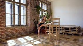 En ung nådballerina i den svarta ballerinakjolen som gör sträcknings- och uppvärmningsövningar på balsalen Behagfull tonårs- flic lager videofilmer