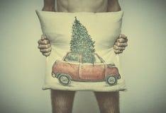 En ung naken man täcker hans hane med en kudde med en themed modell för jul affär efter nytt år royaltyfri fotografi