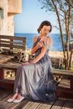 En ung nymphet sitter i en klänning på en bänk med havet på bakgrunden och drar fjädrarna på hennes klänning Royaltyfria Bilder