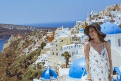 En ung och attraktiv kvinna i en vit klänning och en svart hatt som går på staden av Oia, ö av Santorini, Grekland Begrepp - av Royaltyfri Foto