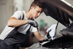 En ung och attraktiv mekaniker kontrollerar en oljanivå av en bilmotor royaltyfria foton
