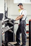 En ung och attraktiv mekaniker ler, medan arbeta på en bilservice genom att använda en dator royaltyfri bild