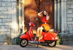 En ung och lycklig brunett på en gammal röd sparkcykel Royaltyfri Foto
