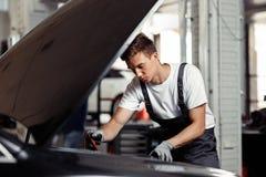 En ung och qulified mekaniker gör hans jobb på en bilservice: kontrollera resultaten av hans arbete arkivbild